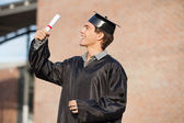 Man In Graduation Gown Looking At Certificate On Campus — Stok fotoğraf