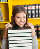 Female Student Resting Chin On Piled Books In Library — Stock Photo