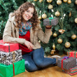 Woman With Presents Sitting Against Christmas Tree — Φωτογραφία Αρχείου