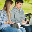 Friends With Laptop And Book Sitting In Campus — Stock Photo