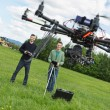 Stock Photo: Engineers Flying UAV Helicopter in Park