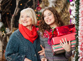 Mother And Daughter With Christmas Presents In Store — Stock Photo