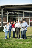 Students With Teacher Discussing Over Book On Campus — Stock Photo