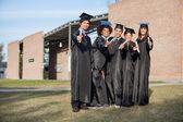 Estudantes universitários mostrando diplomas em pé no campus — Fotografia Stock