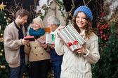 Žena držící vánoční dárek s rodinou v pozadí — Stock fotografie