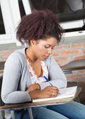 Aluno escrevendo o exame no balcão na sala de aula — Fotografia Stock