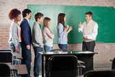 Teacher Gesturing Thumbsup Sign To Successful Student At Classro — Stock Photo