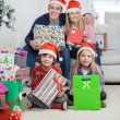 Family In Santa Hats Holding Christmas Gifts — Stock Photo