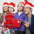 Family In Santa Hats With Christmas Gift — Stock Photo #33780697