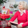 Senior Woman With Christmas Present Looking Away — Stock Photo
