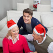 Smiling Man With Parents Holding Christmas Gift — Stock Photo #33780981