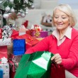 Woman Looking In Bag While Sitting By Christmas Gifts — Stock Photo