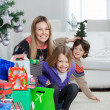 Mother With Children Sitting By Christmas Gifts — Stock Photo #33782199