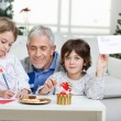 Boy Showing Letter While Grandfather Assisting Girl — Stock Photo #33782207