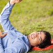 Stock Photo: College Student Holding Mobilephone While Lying On Grass At Camp