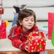 Foto Stock: Boy With Christmas Present Lying On Floor