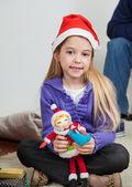 Jeune fille au chapeau de santa holding jouet — Photo