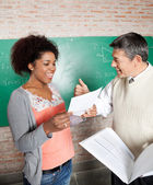 Teacher Gesturing Thumbsup To Successful Student In Classroom — Stock Photo