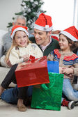 Siblings And Father With Christmas Presents — Stock Photo