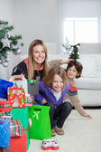 Mother With Children Sitting By Christmas Gifts — Stock Photo