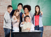 Students And Professor Gesturing Thumbsup At Desk In Classroom — Stock Photo