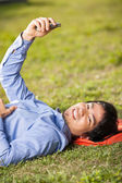 College Student Holding Mobilephone While Lying On Grass At Camp — Stock Photo