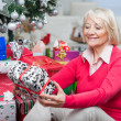 Senior Woman Looking At Christmas Gift — Stock Photo