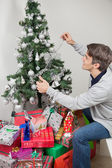 Man Decorating Christmas Tree With Fairy Lights At Home — Stock Photo