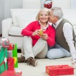 Stock Photo: WomHolding Christmas Present While MAbout To Kiss Her