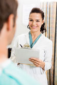 Doctor With Clipboard Standing By Patient — Stock Photo