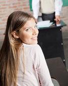 Sınıfta masada oturan üniversite öğrencisi — Stok fotoğraf
