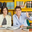 Stock Photo: Student Gesturing Thumbsup While Friend Reading Book In Library