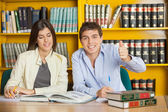 Student Gesturing Thumbsup While Friend Reading Book In Library — Stock Photo