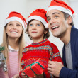 Happy Family With Christmas Gift Looking Away — Stock Photo