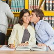 Man Kissing Woman In College Library — Stock Photo