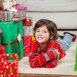 Happy Boy Lying Besides Stacked Christmas Gifts — Stock Photo