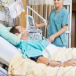 Nurse Examining Young Patient Lying On Bed — Stock Photo