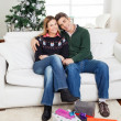 Stock Photo: Couple With Christmas Presents On Floor