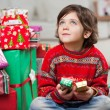 Thoughtful Boy Sitting By Christmas Gifts — Stock Photo