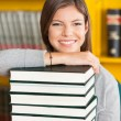Happy Woman Resting Chin On Stacked Books In Library — Stock Photo