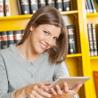 Woman With Digital Tablet Sitting Against Bookshelf In Library — Stock Photo
