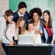 Students Standing With Classmates While Teacher Teaching On Lapt — Stock Photo #33908639