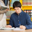 Student Writing In Book At College Library — Stock Photo #33909091