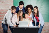 Students Standing With Classmates While Teacher Teaching On Lapt — Stock Photo