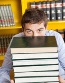 Male Student Peeking Over Stacked Books In Library — Stock Photo