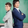 Male Students Standing Hands Folded Against Greenboard In Classr — Stock Photo