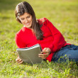 Woman Reading Book While Relaxing On Grass At Campus — Stock Photo