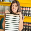Confident Student Sitting With Stacked Books In Library — Stock Photo