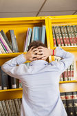 Frustrated Man Standing Against Bookshelf In Library — Stock Photo