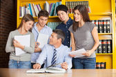 Teacher Pointing At Book While Discussing With Students In Libra — Stock Photo